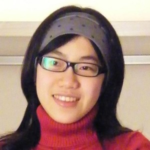 Photo of Mumico from Taiwan. She is wearing a gray polka-dotted headband and a red turtleneck sweater.