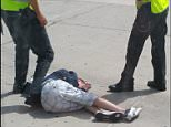 BNPS.co.uk (01202 558833) Pic: KeiranCampbell/BNPS This is the dramatic moment a British holidaymaker was pinned down by police on an airport apron after causing havoc among passengers on board a flight. Spanish police were waiting to detain the aggressive holidaymaker as the Ryanair plane landed in Tenerife after he was said to have acted inappropriately towards women passengers on board. The incident happened on a 7am flight from Bournemouth to Tenerife on Tuesday.