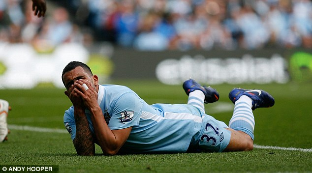 Pain game: Tevez winces in agony after being struck by Barton
