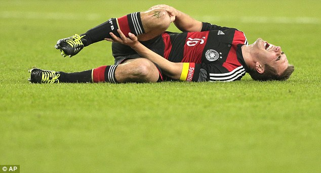 Ouch: Germany and Bayern Munich captain Philipp Lahm lies on the turf after a heavy challenge