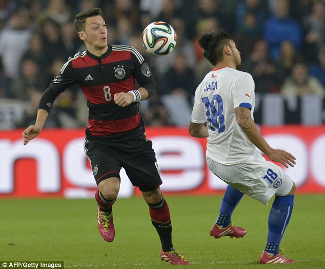 On the ball: Ozil lifts the ball over the head of Gonzalo Jara during the first half