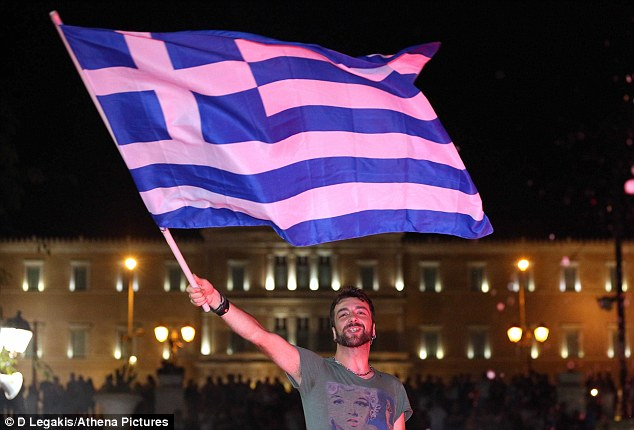 A man waves a Greek flag infront of the Parliament as the country reacted to the result of the referendum