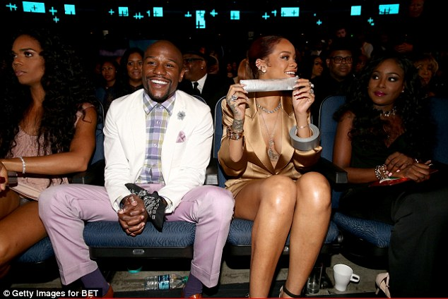 The boxing champion smiles while sat alongside Rhianna as the 2015 BET Awards in June