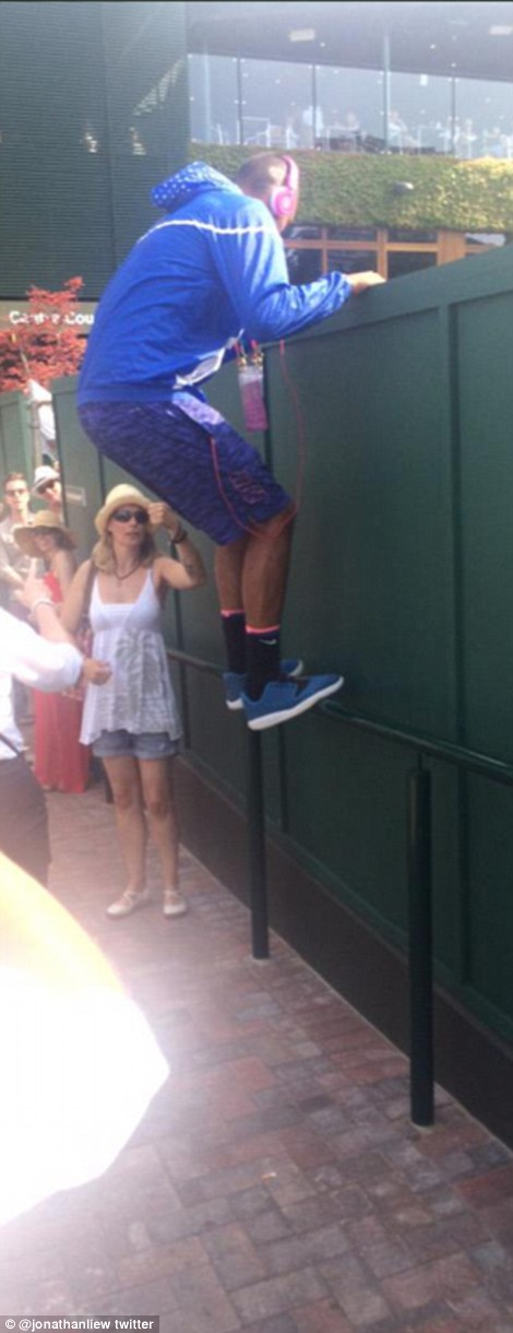Australian tennis star Nick Kyrgios was snapped by a fan at Wimbledon climbing onto a fence for a better view of the action