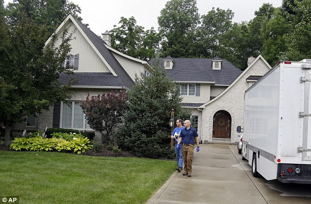 Disturbing: Investigators wrote that many of the videos found in the raid on Taylor's home appeared to be shot in bedrooms and bathrooms at his former and current homes. Above, investigators outside Fogle's house on Tuesday