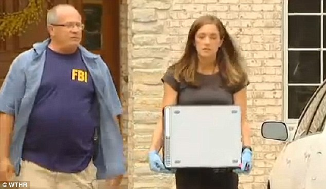 Looking for evidence: A female investigator is seen taking a computer hard-drive out of Fogle's home Tuesday morning