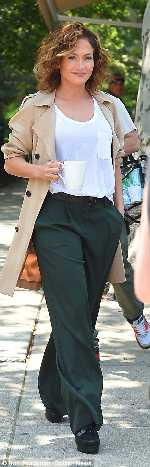 Dress detective:To play her character Harlee McCord, Jlo wore a pair of wide leg green trousers with a white T-shirt tucked in at its high waist and added a long trench