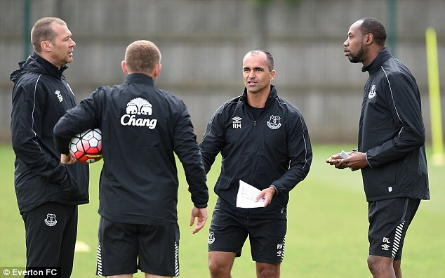 Everton manager Roberto Martinez (middle right) talks tactics with his fellow coaches during a training session