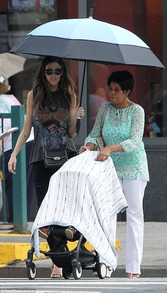 Taking control: Sandi showed off her grandmother duties as she pushed her grandson around in his pram