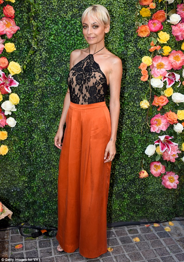 Sheer delight: Nicole looked stunning in a black lace halter top and a pair of bright orange trousers on Tuesday as she hosted a promotional event for the second season of her VH1 series at her store