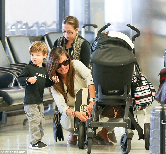 Doting mother: Vanessa happily leaned down to adjust a piece of her daughter's stroller