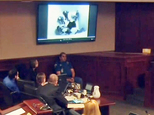 In this image taken from video, accused Colorado theater shooter James Holmes, on the far left, watches an evidence video of himself in a jail cell during his trial, in Centennial, Colo., Friday, July 10, 2015. Holmes is in the center of the video under a blanket after being covered by the officers surrounding him. Holmes has pleaded not guilty by reason of insanity to killing 12 people and injuring 70 others in the July 2012 shooting at a suburban Denver movie theater. (Colorado Judicial Department via AP, Pool)