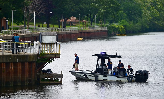 Search: Police are seen combing the river to find Aaden's body after he was thrown off a bridge on Sunday. He was  found on Tuesday