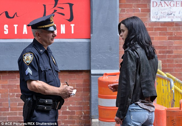 In trouble: Krysten's smile faded as she hopped back into character, and was pictured in what appeared to be a confrontation with a police officer