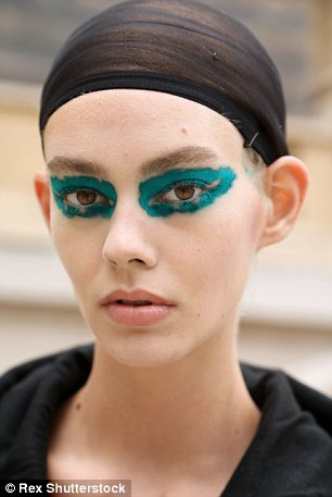 Striking: Models set to take part in the Haute Couture A/W15 show had their faces painted with bright hues