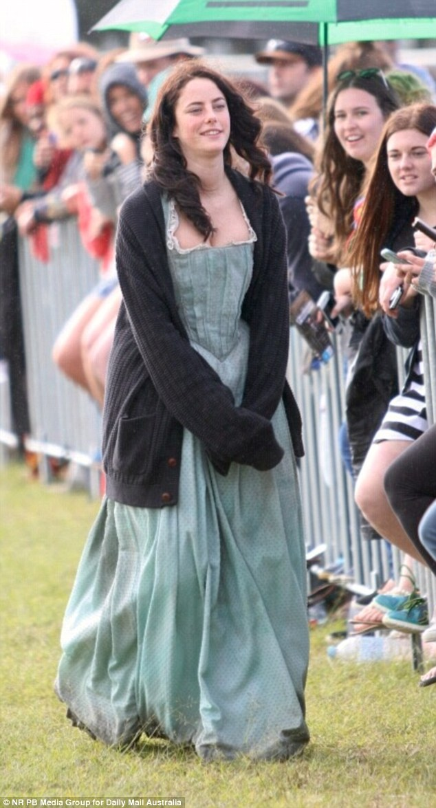 Kicking back: The 23-year-old was dressed in a mid-18th century style gown and a thick knitted jacket as she braved the cool winter weather