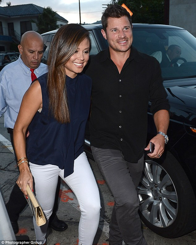 Beaming: The brunette beauty grinned while making a stylish entrance in white trousers and a midnight blue tank top