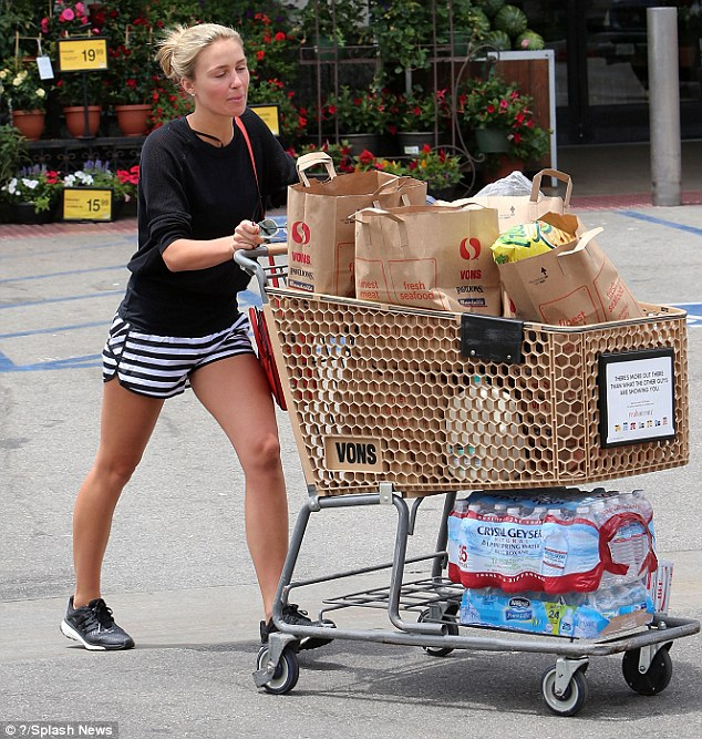 Bronzed beauty: The WAGfinished HER look with a pair of black Adidas trainers, which no doubt provided a welcome source of comfort as she pushed along her trolley, which was jam-packed with grocery bags
