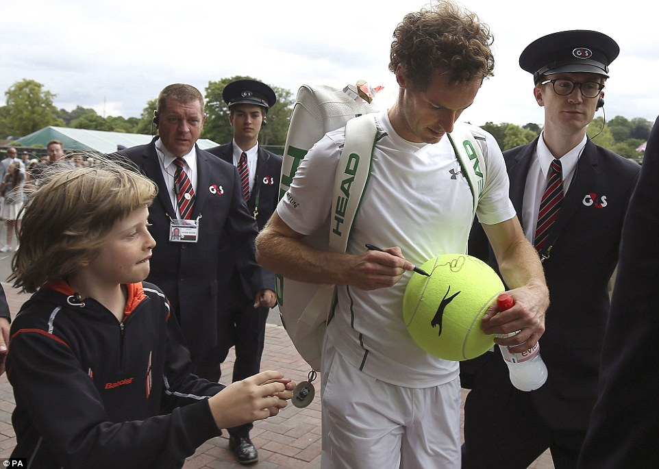 One for you: Murray cheerfully signed an oversized tennis ball belonging to young fan, Noah Irvin, 10, as he made his exit