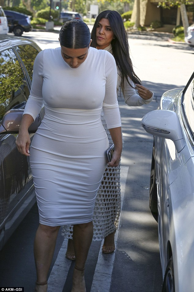 Check it out: Kim looked down at her burgeoning belly, which was clear for all to see in the racy frock