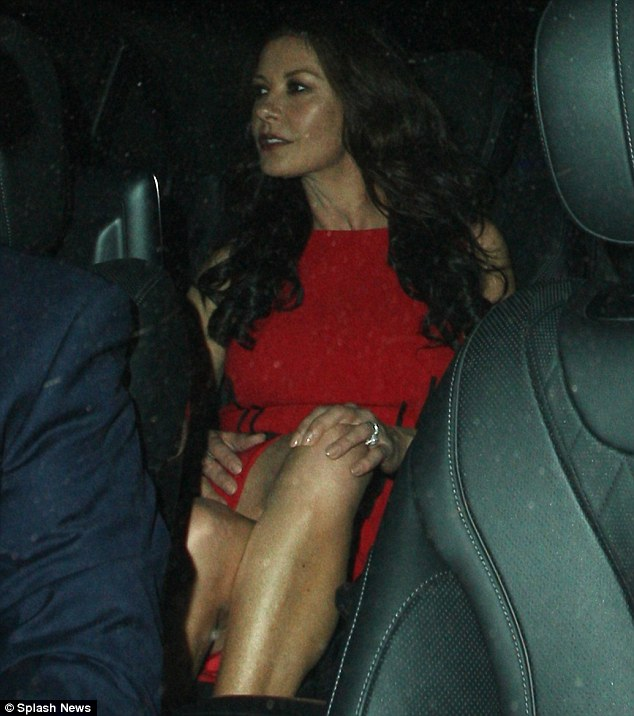Best supporting wife: Catherine Zeta-Jones looked stunning in red as she was spotted leaving dinner in London with husband Michael Douglas on Tuesday