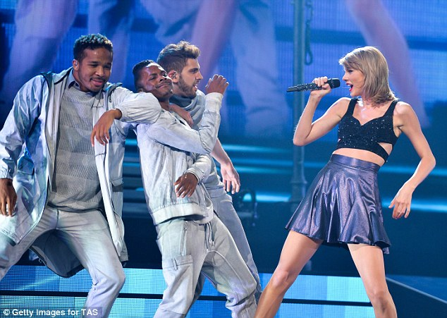 Girls: Other stage costumes embrace a more feminine look, as leggy Swift performed songs in a number of flirty foil skater skirts in blue and purple
