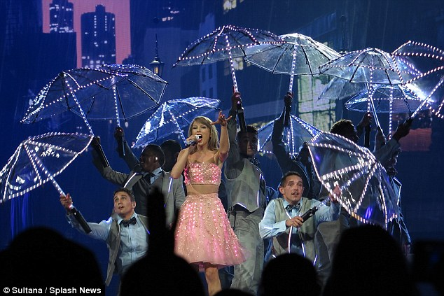 Let it rain: Tyalor opted for an LED dress which lit up as her dancers held up umbrellas