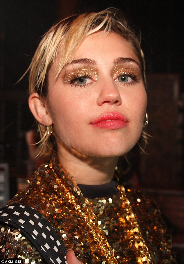 Razzle dazzle em: She paid close attention to detail in standing out with glittering eyelids and a gold sequin dress