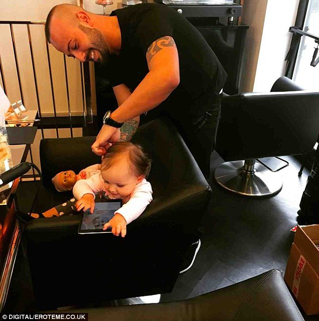 Getting a trim: Sophia sat in the plush stylist's chair as she got a haircut, with the one-year-old entertaining herself with an iPad