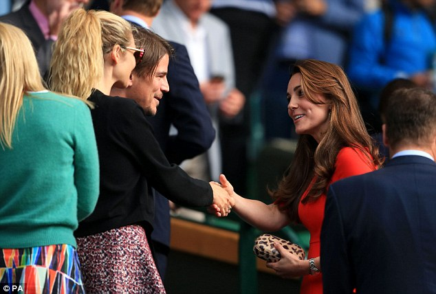 Winning smile: Lovely Kate, 33, looked impressive in a bright orange dress as she stepped up through the Royal Box to greet the acting pair