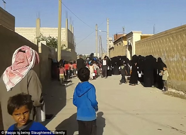 Starving: Hundreds of young boys and women appear to be queuing for food in ISIS's adopted capital of Raqqa in Syria during the holy month of Ramadan