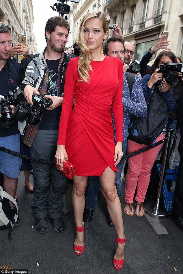Keeping it classy: Standing tall in red strappy heels, the model toted her belongings in an embellished clutch