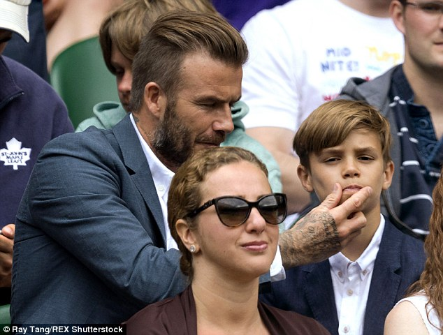 Doting dad: The father-of-four was spotted licking his thumb before rubbing his middle son's chin in a tender display of affection - but Romeo didn't seem too impressed