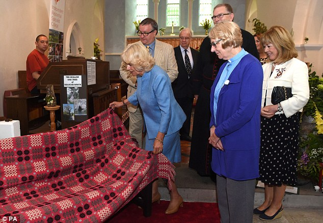Getting involved: The Duchess of Cornwall unveils a commemorative bench during a visit to the Flower Festival at St Barnabas Church in Rhandirmwyn, Llandovery