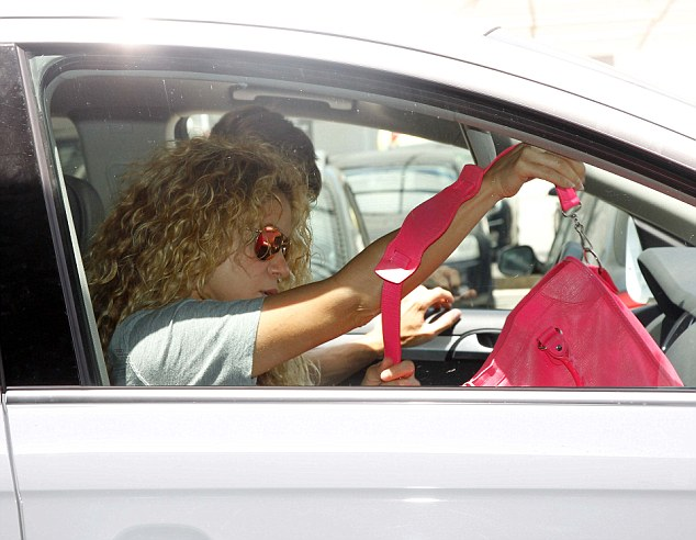 Holiday mode: In the front of the vehicle, Shakira fiddled with her bright pink handbag