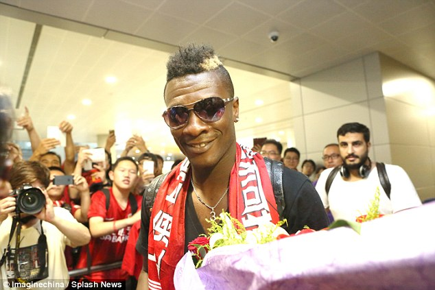 Ghana skipper Asamoah Gyan is all smiles as he arrives in China ahead of his big-money move