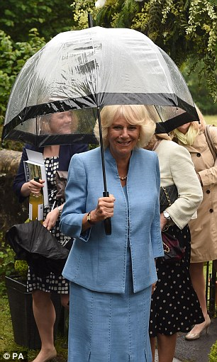 Staying dry: The Duchess of Cornwall during a visit to the Flower Festival at St Barnabas Church in Rhandirmwyn, Llandovery on the third day of her visit to Wales
