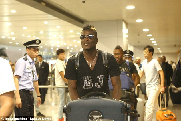 The former Sunderland star, pictured wheeling his suitcase, will earn over£163,000-a-week atShanghai SIPG
