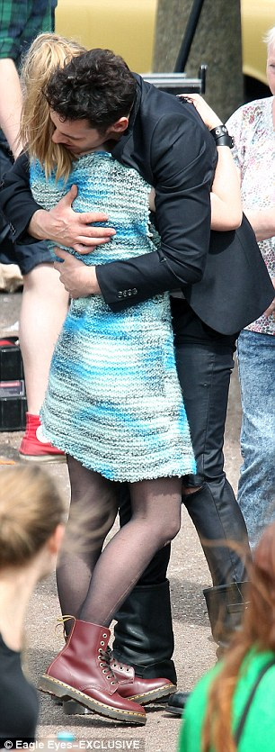 Hugging it out: Jonathan,  in character as Strummer, was seen embracing a fan