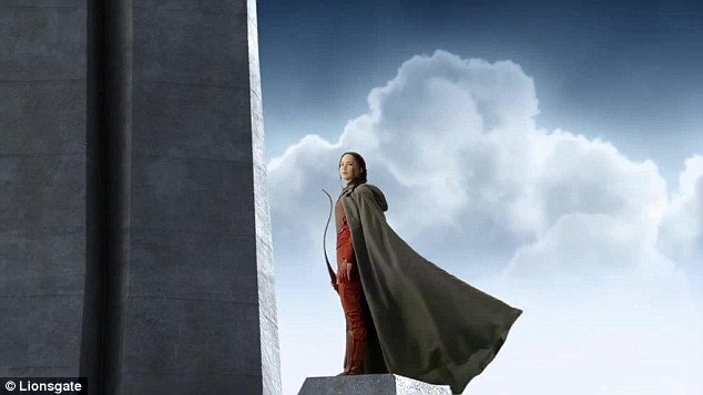 Addressing her subjects: Katniss appears to be quite the hero in a fiery red super suit as she stands among the clouds in the video, only turning her head to face the camera after it had panned back a bit