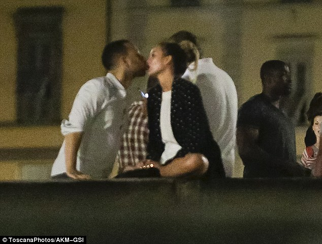 So in love: Chrissy, still sat on the bridge wall, made sure to show her affection as she and her man went in for a kiss