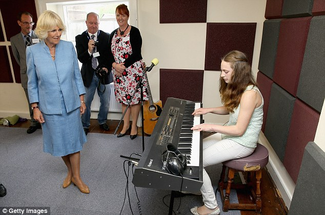 Hitting the right notes: Camilla watches a performance during a visit to the Llandovery YMCA, which was founded in 1990 to provide a safe meeting place for the young people of the town and surrounding villages