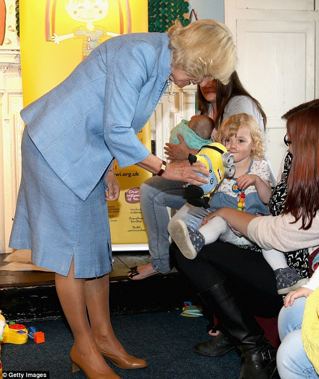 Meet and greet: The Duchess of Cornwall meets a young girl with a 'Minions' toy during a visit to the Llandovery YMCA