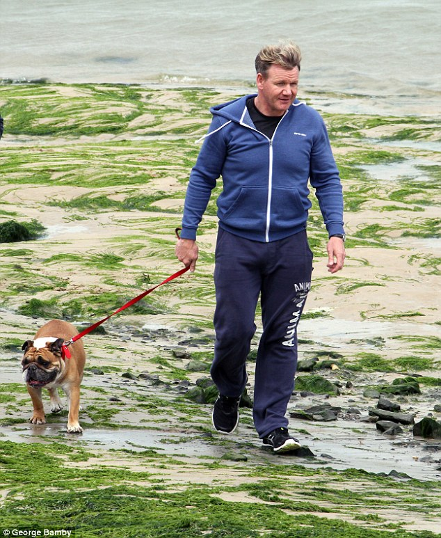 Feeling cold: While holding onto his dog, Gordon later covered up in a large blue hoodie for added warmth
