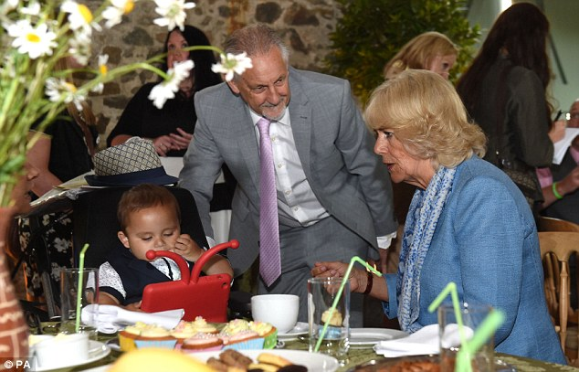 The Duchess of Cornwal meets Pavil Mohammady, three, and his foster dad Ray Stephens during a tea party for children from the Ty Hafan Hospice at the Llwynywermod estate