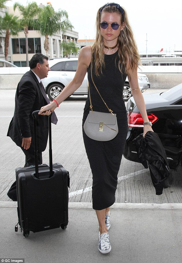 Super chic: The 26-year-old teamed the sleeveless dress with black-and-white slip-on sneakers and she carried a soft black jacket in one hand as she pulled her carry on luggage with the other.