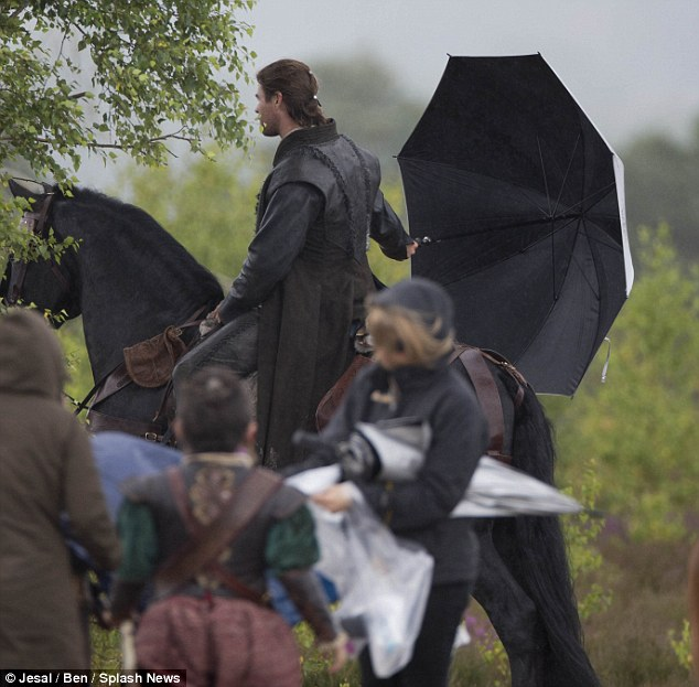 Keeping covered: The actor shielded himself from the rain with an umbrella during a break from filming