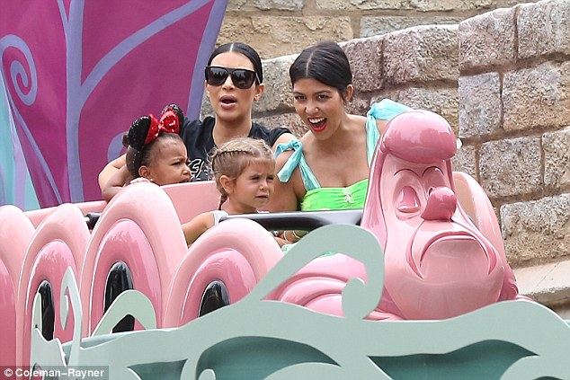 Good times: Kim sat behind Kourtney and Penelope with North as they took one of the cute rides