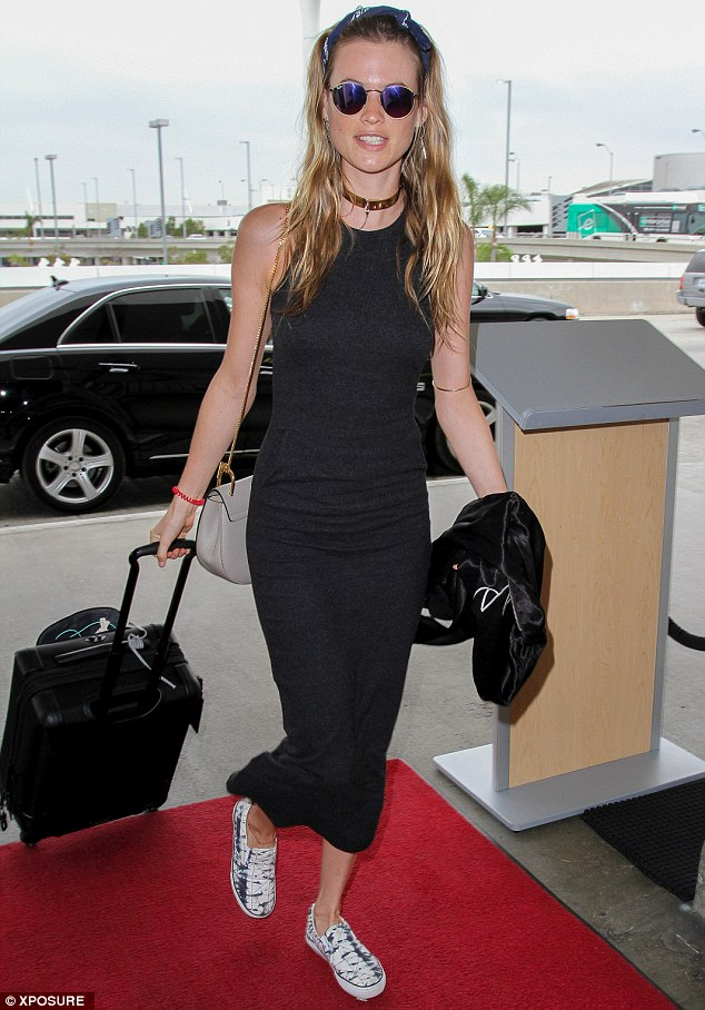 Different kind of red carpet: Supermodel Behati Prinsloo sizzled in a skin-tight, ankle-length black dress as she turned up at the airport for a flight out of Los Angeles on Wednesday