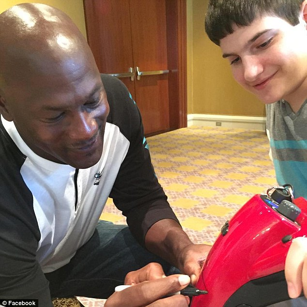 Visit from a star: Tzvi, 18, has the worst symptoms of his siblings, and went from walking to needing a motorbike in just three months when he was entering high school. Pictured above getting his scooter signed by Michael Jordan